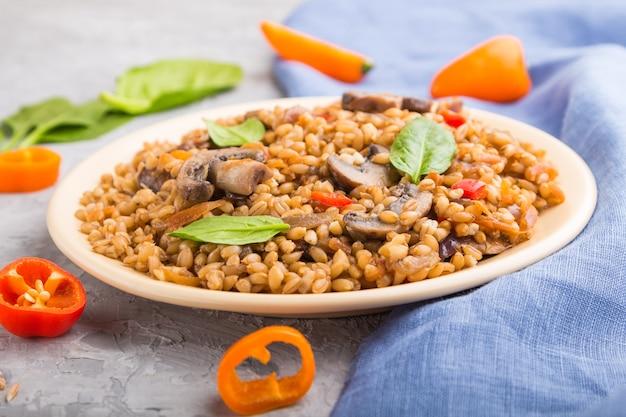 灰色のコンクリート表面と青いリネン織物のセラミックプレートに野菜とキノコが入ったスペルト小麦のお粥
