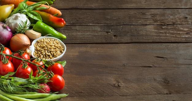 ボウルに綴り、茶色の木製のテーブルで新鮮な生野菜をコピースペースでクローズアップ