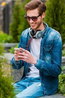 屋外でのんびりとした時間を過ごします。携帯電話を持って笑顔のハンサムな若い男