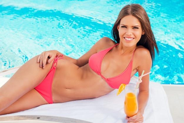 평온한 시간을 수영장에서 보내고 있습니다. 비키니를 입은 아름다운 젊은 여성이 칵테일을 들고 수영장 근처의 갑판 의자에서 휴식을 취하면서 웃고 있습니다.