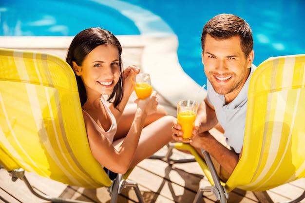 Беззаботно проводить время у бассейна. счастливая пара, держащая коктейли и улыбаясь, сидя на шезлонгах у бассейна