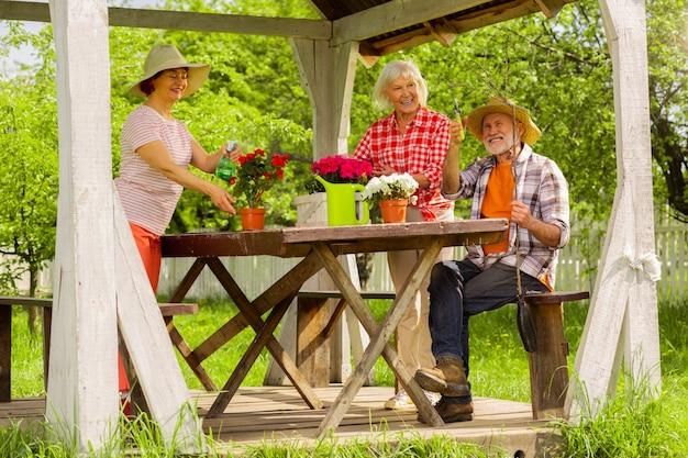 Проведите день на улице. красивый мужчина и женщина на пенсии проводят день на улице, заботясь о цветах