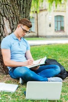 毎分勉強に費やします。芝生の上や大学の建物の前でメモ帳に何かを書いている眼鏡をかけた自信のある男子生徒