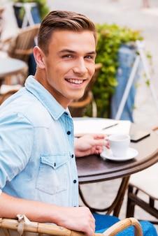 カフェで楽しい時間を過ごします。歩道のカフェに座ってコーヒーを飲み、肩越しに見ている陽気な青年の背面図