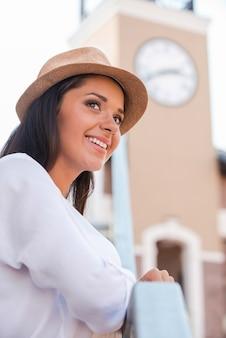 야외에서 좋은 시간을 보내고 있습니다. 펑키 모자를 쓴 아름다운 젊은 여성이 야외에서 멀리 바라보고 웃고 있는 낮은 각도