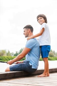 Проводите вместе хорошо время. низкий угол обзора веселых отца и сына, вместе ловящих рыбу на набережной