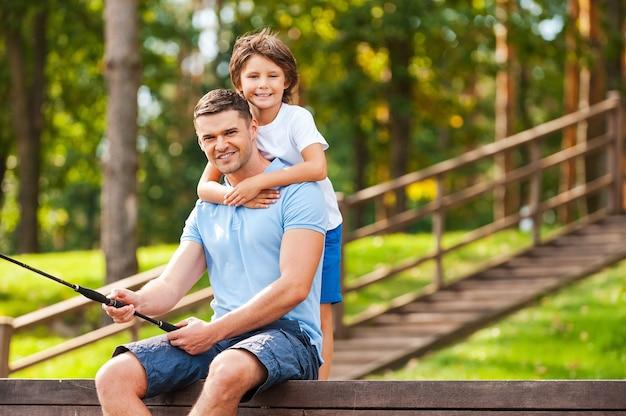 Хорошо проводить время с отцом. счастливый отец и сын вместе ловят рыбу и улыбаются, сидя на набережной