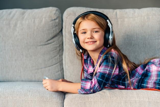 Отлично проводить время дома. красивая маленькая девочка в наушниках с улыбкой смотрит в камеру, лежа на диване у себя дома