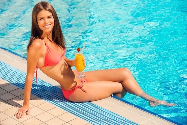 수영장 옆에서 즐거운 시간을 보내고 있습니다. 비키니를 입은 아름다운 젊은 여성이 칵테일을 들고 수영장 옆에 앉아 미소로 카메라를 바라보고 있습니다.