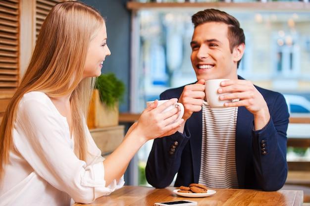 Прекрасно проводим время вместе. красивая молодая пара разговаривает друг с другом и улыбается, наслаждаясь кофе в кафе вместе