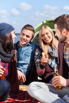 Прекрасно проводим время вместе. группа молодых веселых людей пьет пиво и разговаривает во время кемпинга на берегу реки