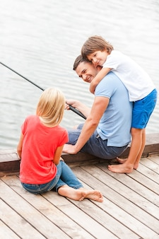 Прекрасно проводим время вместе. счастливый отец рыбачит со своими детьми, сидя на берегу реки вместе