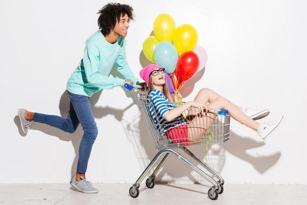 Прекрасно проводим время вместе. счастливый молодой человек несет свою красивую подругу в тележке для покупок и улыбается во время бега на сером фоне