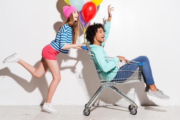 Прекрасно проводим время вместе. счастливые молодые женщины несут своего парня в тележке для покупок и улыбаются во время бега на сером фоне
