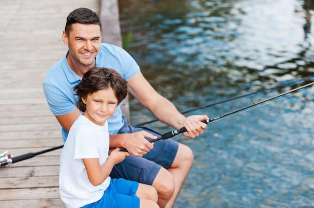 Прекрасно проводим время вместе. вид сверху на отца и сына, которые смотрят в камеру и улыбаются, сидя на набережной с лежащими рядом с ними удочками