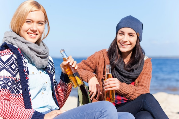 Spending great time together. two beautiful young women holding beer bottles and smiling while sitting on the beach together