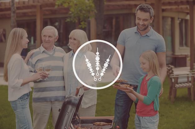 Прекрасное времяпрепровождение с семьей. счастливая семья из пяти человек жарит мясо на гриле на заднем дворе