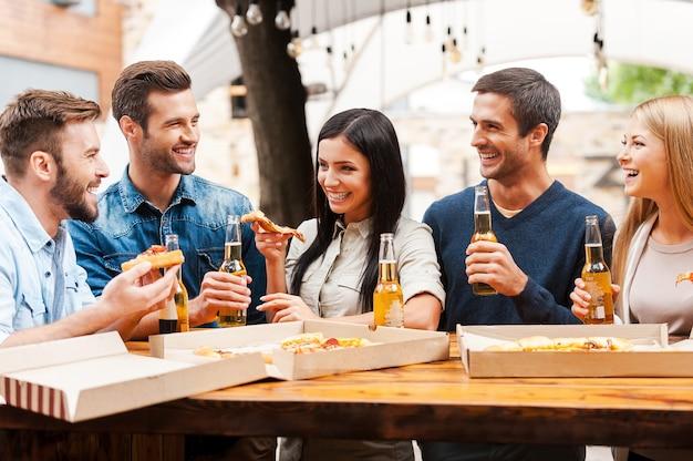友達と素晴らしい時間を過ごします。屋外に立ってピザを食べたり、ビールを飲んだりする楽しい若者のグループ