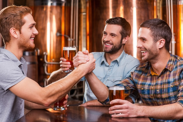 Spending great time with friends. three happy young men in casual drinking beer while sitting in beer pub together