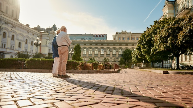 야외에서 함께 서 있는 세련된 노부부와 함께 즐거운 시간을 보내세요