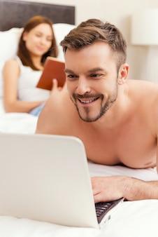 침대에서 여가 시간을 보내고 있습니다. 잘생긴 젊고 셔츠를 입지 않은 남자가 침대에 누워 노트북 작업을 하는 동안 여자가 배경에서 책을 읽는 동안