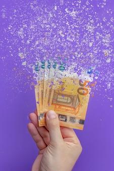お金を使う、すべてのお金を使うのは文盲です。ユーロ紙幣は灰に変わり、紫色の背景に溶けます。縦の写真