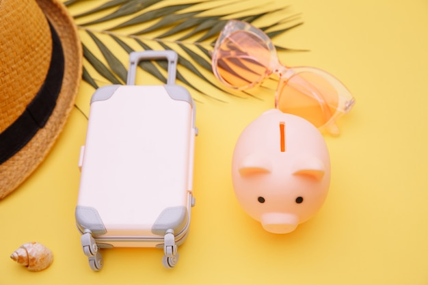 Spending money for tourism. mini travel luggage suitcase with piggy bank on yellow table.