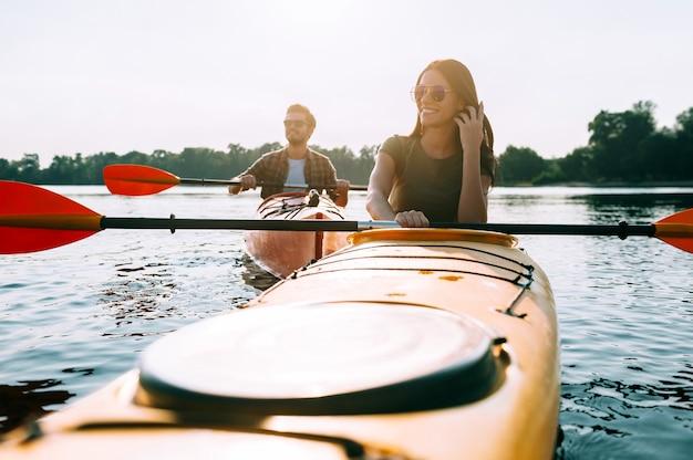一緒に充実した時間を過ごします。一緒に湖でカヤックと笑顔の美しい若いカップル