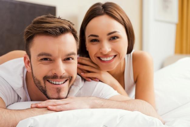 양질의 시간을 함께 보내고 있습니다. 함께 침대에 누워있는 동안 서로 결합하는 아름다운 젊은 사랑의 부부