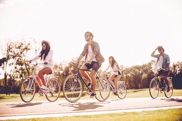 一緒に充実した時間を過ごします。道路に沿って自転車に乗って幸せそうに見える若者のグループ