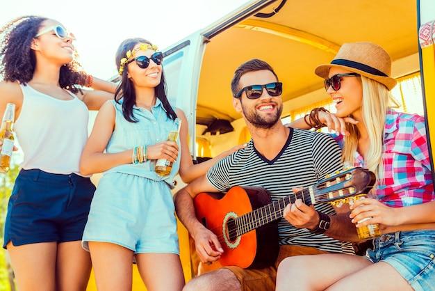 Проведите время с друзьями. красивый молодой человек сидит в минивэне и играет на гитаре, в то время как три девушки стоят рядом и улыбаются