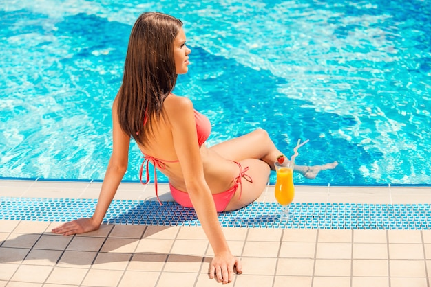 여름 시간을 풀사이드에서 보내고 있습니다. 비키니를 입은 젊은 여성이 수영장 옆에 앉아 칵테일을 마시고 있는 그녀의 뒷모습