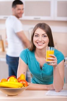 日曜日の朝を一緒に過ごす。台所のストーブに寄りかかって、背景に立って笑顔の男がオレンジジュースとグラスを保持している美しい若い女性