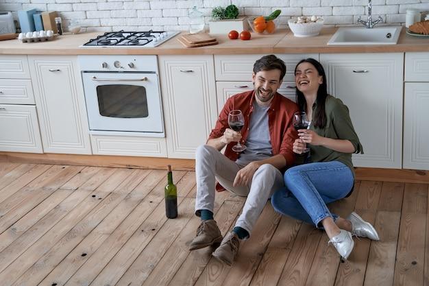 家で時間を過ごす若い幸せなロマンチックなカップルの妻と夫が床に座って