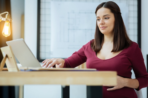 Spending time at home. close up of young attentive woman using a laptop while sitting at the table and expressing interest