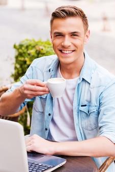 カフェで過ごす時間。歩道のカフェに座ってラップトップに取り組んで、コーヒーを飲む陽気な若い男