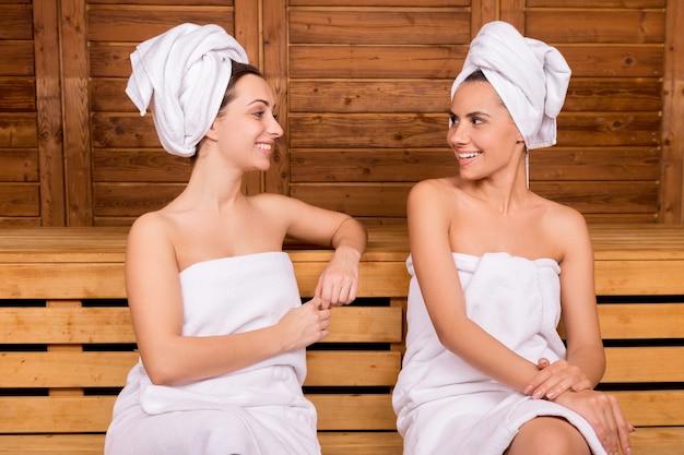 Проведение времени в сауне. две привлекательные женщины, завернутые в полотенце, разговаривают друг с другом во время отдыха в сауне