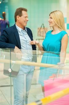 쇼핑몰에서 시간을 보내고 있습니다. 쾌활한 성숙한 부부는 쇼핑몰에 서서 서로 이야기하고 몸짓