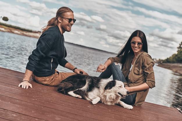 Проводите время вместе. красивая молодая пара играет с собакой, сидя на берегу озера на открытом воздухе