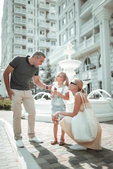 家族と過ごす時間。噴水の前で夏の朝に彼らの小さな娘と一緒に歩いている幸せな夫婦。