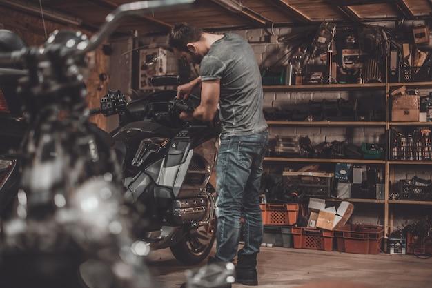 Проводите время с велосипедами. уверенный молодой человек, ремонтирующий мотоцикл в ремонтной мастерской