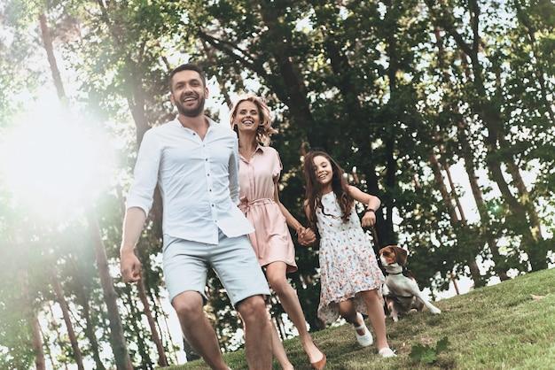 가족과 함께 시간을 보내는 것. 개가 손을 잡고 공원에서 뛰면서 웃고 있는 3명의 행복한 젊은 가족