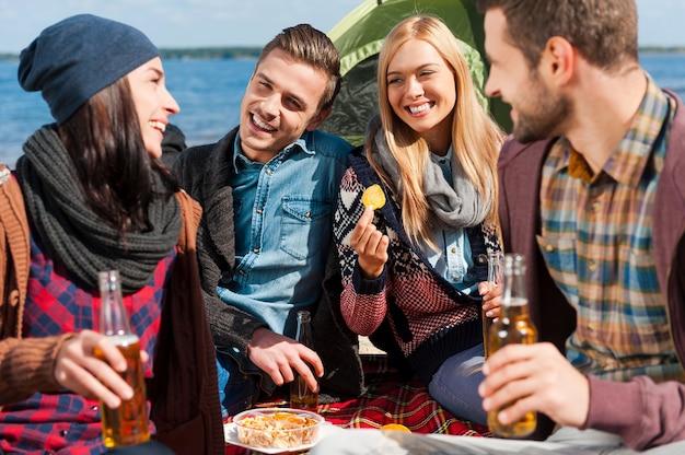 Проводить время с друзьями. группа молодых веселых людей пьет пиво и разговаривает во время кемпинга на берегу реки
