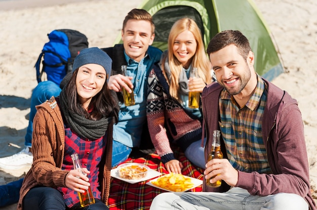 Spending time with friends. group of young cheerful people drinking beer and talking while camping at the riverbank