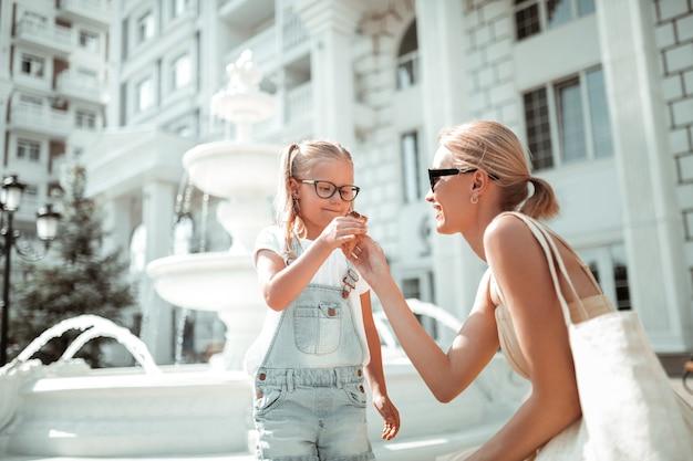 お母さんと過ごす時間。夏の朝、一緒に散歩中に娘にアイスクリームコーンをあげる母親。