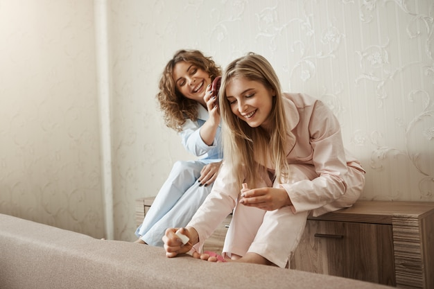 Spending weekend with sister is better than alone. charming happy curly-haired woman in pyjamas combing her friend hair while she is painting fingernails on feet, laughing and talking about life