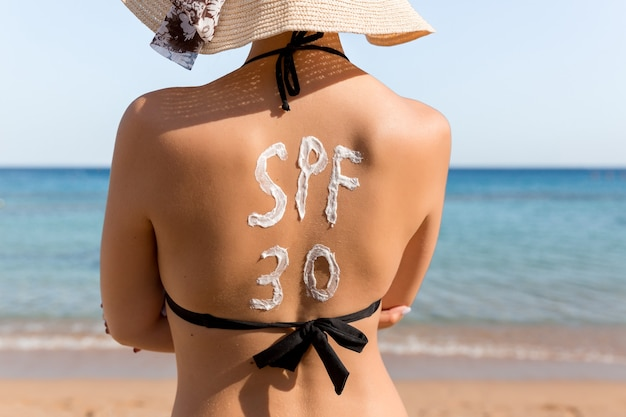 Spf 30 단어는 해변에서 휴식을 취하는 여성의 등에 선크림으로 그려져 있습니다.