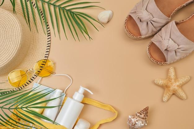 ストリングバッグ、サングラス、貝殻、ヒトデのspf日焼け止めクリーム、夏の靴、ベージュの砂の表面にサージカルマスク Premium写真