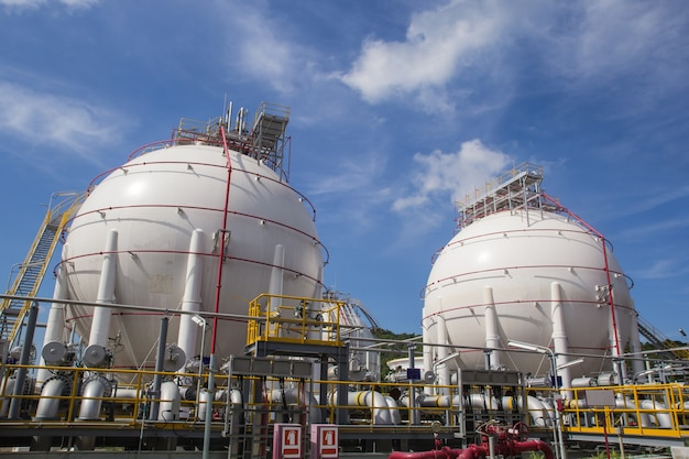 Сферические резервуары белого цвета, содержащие топливный газ, нефтеперерабатывающие заводы, голубое небо.