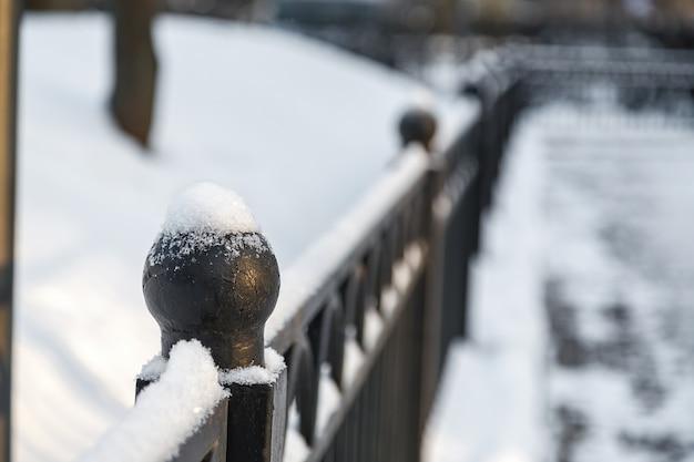 雪の中で金属の装飾的なフェンスの球形の上部。